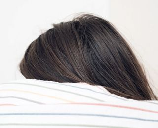 A person feeling shame, hiding face under covers